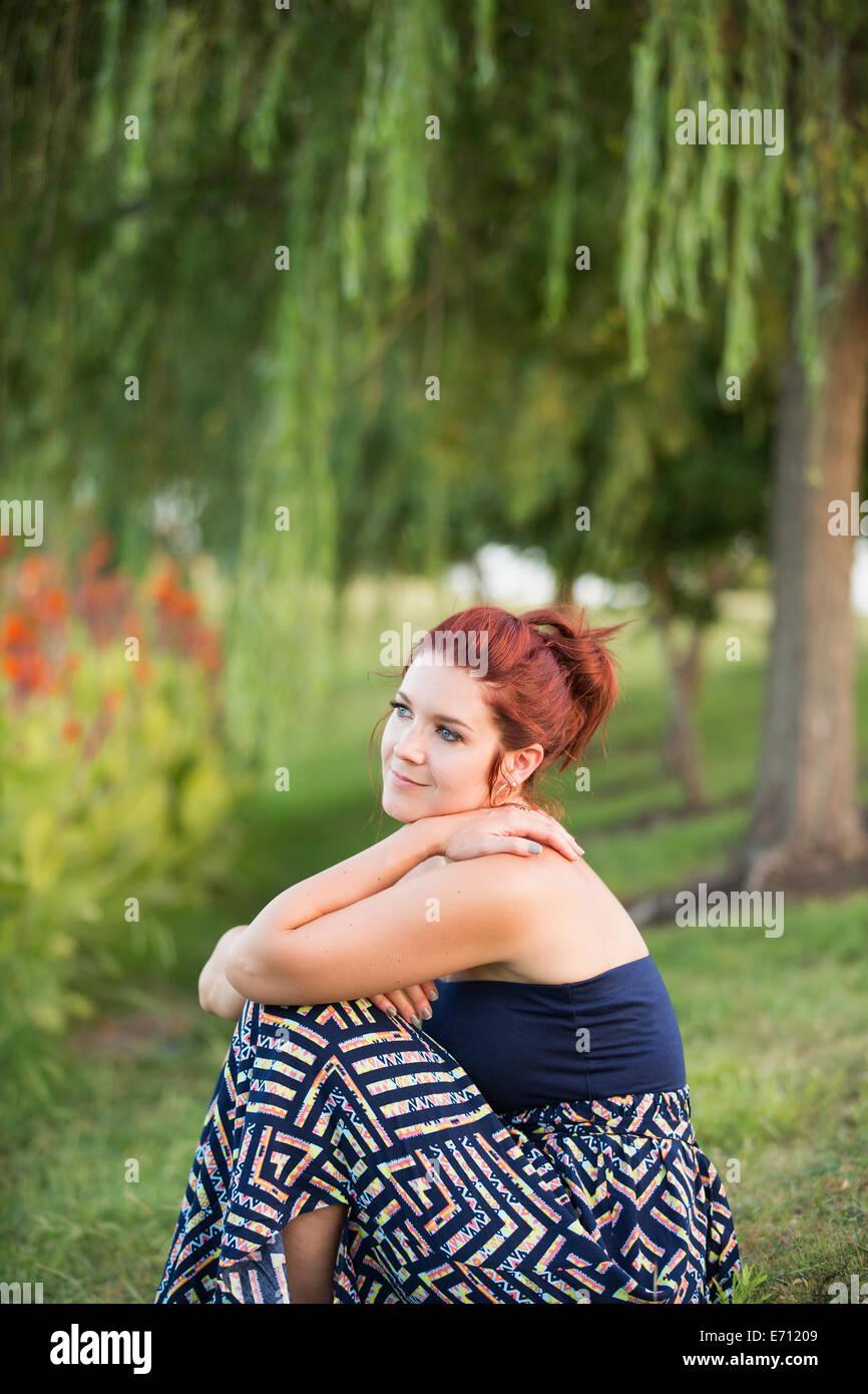 Una donna seduta sotto un salice piangente albero. Immagini Stock