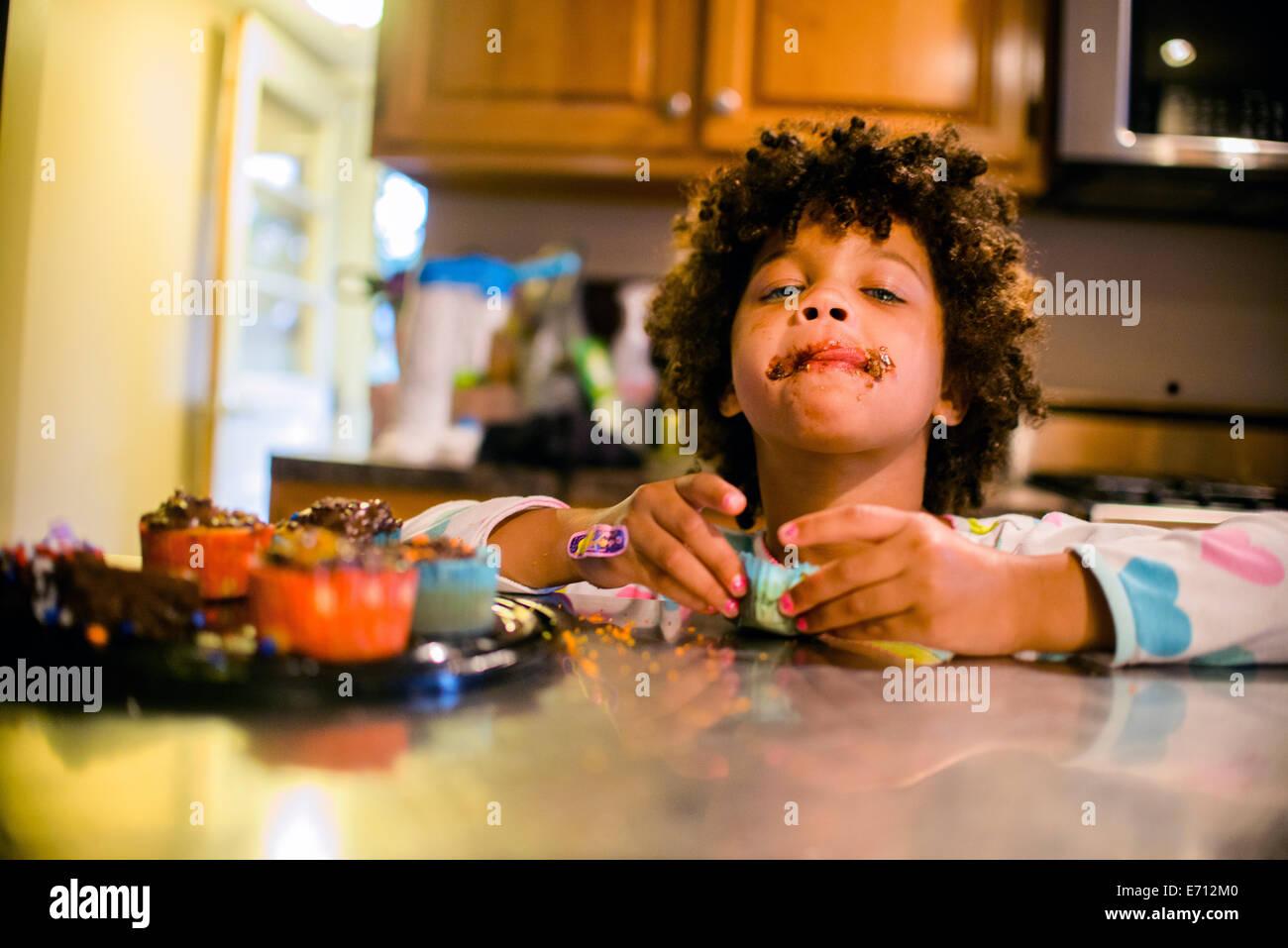Ritratto di ragazza con ricoperta di cioccolato bocca di mangiare i tortini Immagini Stock