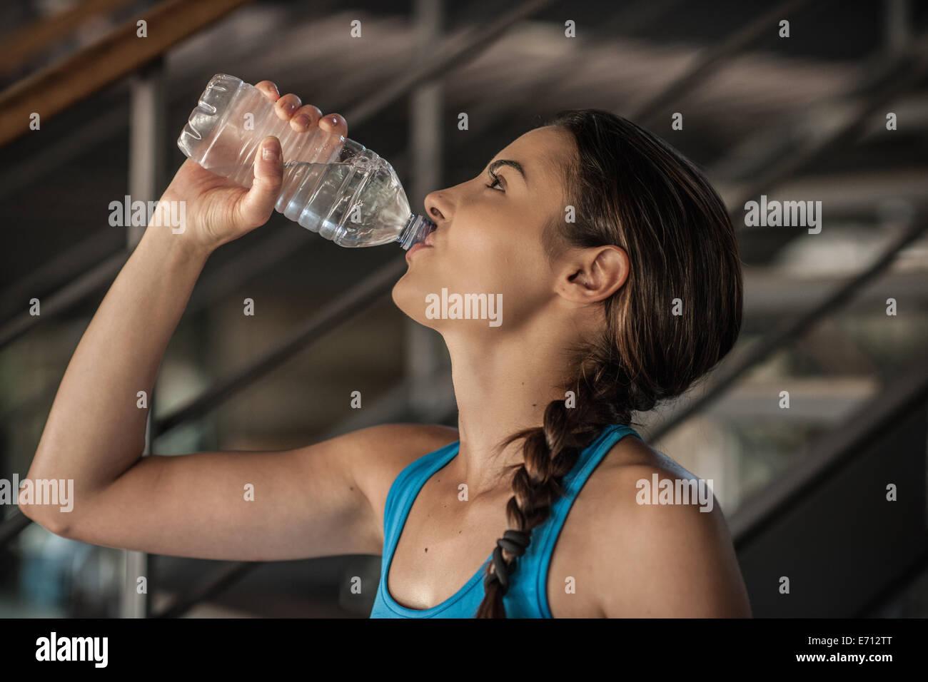 Giovane donna acqua potabile da bottiglia Immagini Stock