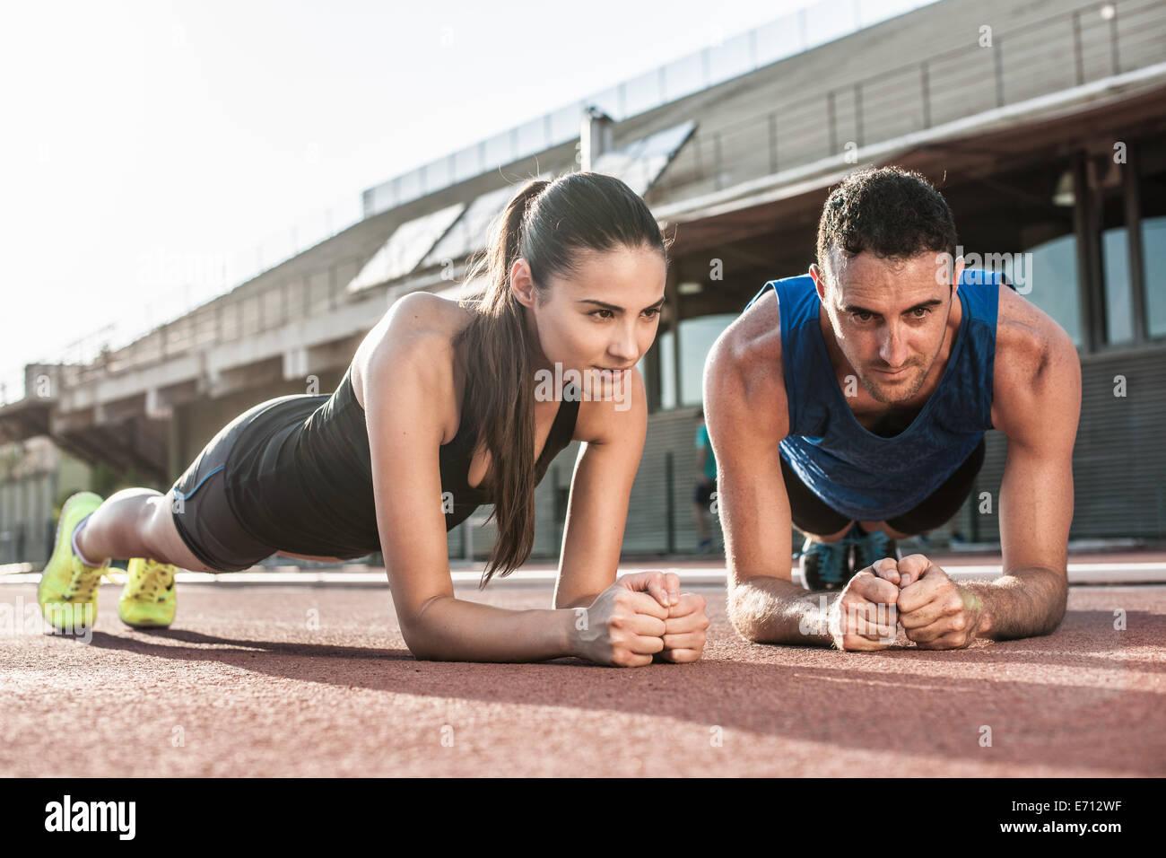 L uomo e la donna facendo esercizi tavoloni Immagini Stock