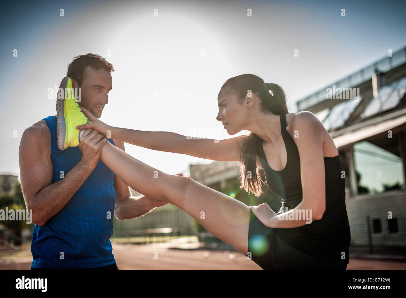 L'uomo aiutando donna gamba estensibile Foto Stock