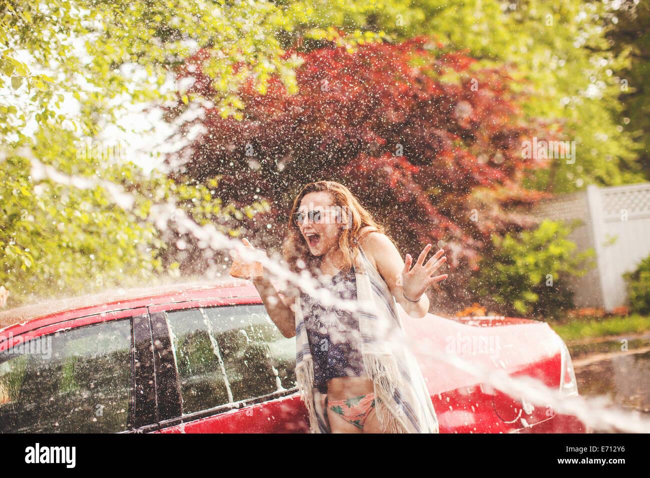 Giovane donna che viene spruzzato con acqua Immagini Stock
