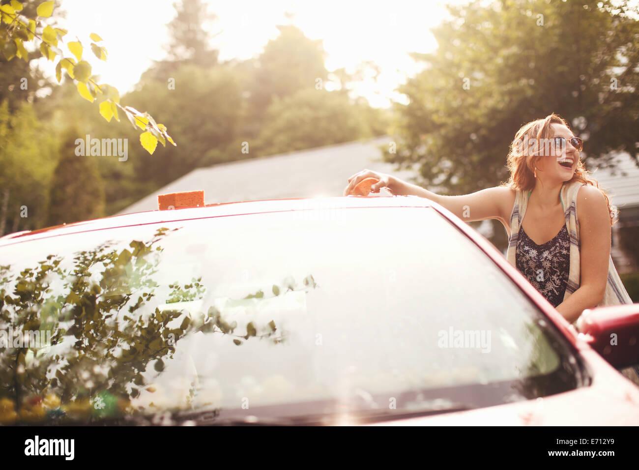 Giovane donna il lavaggio auto Immagini Stock