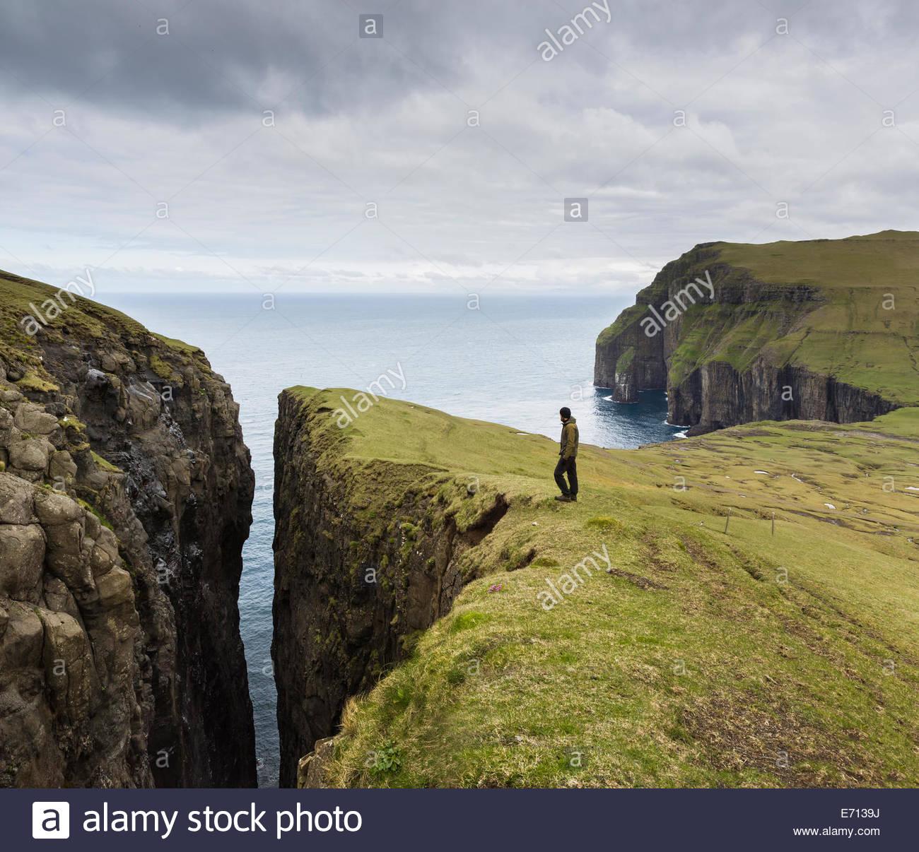 Uomo in piedi in cima alla scogliera, Asmundarstakkur, Isole Faerøer, Danimarca Immagini Stock