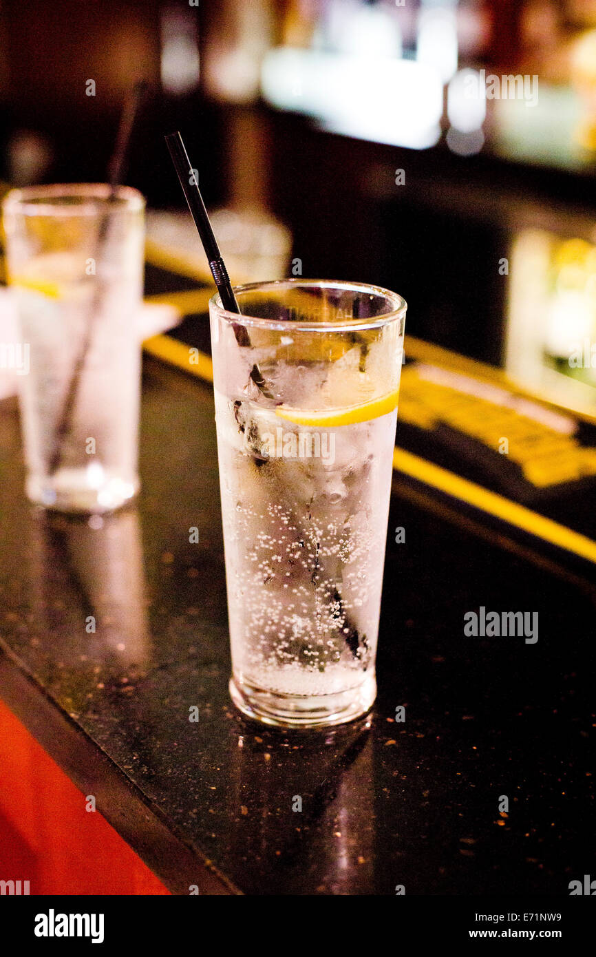 Gin Tonic con un slce di limone, ghiaccio nero e paglia. Prese su 29/08/2014 Immagini Stock