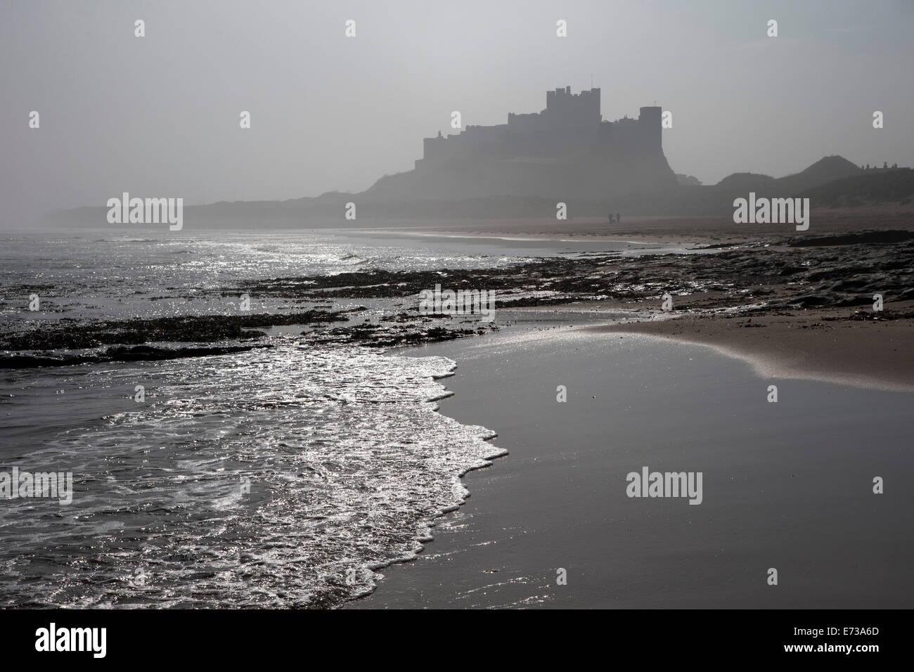 Onde che si infrangono a spiaggia Bamburgh guardando verso il castello di Bamburgh in una nebbiosa mattina, Northumberland, England, Regno Unito Foto Stock
