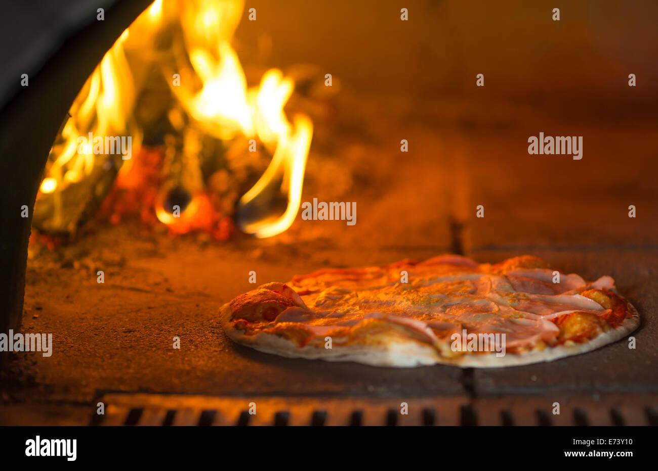 La cottura della pizza in forno tradizionale Immagini Stock