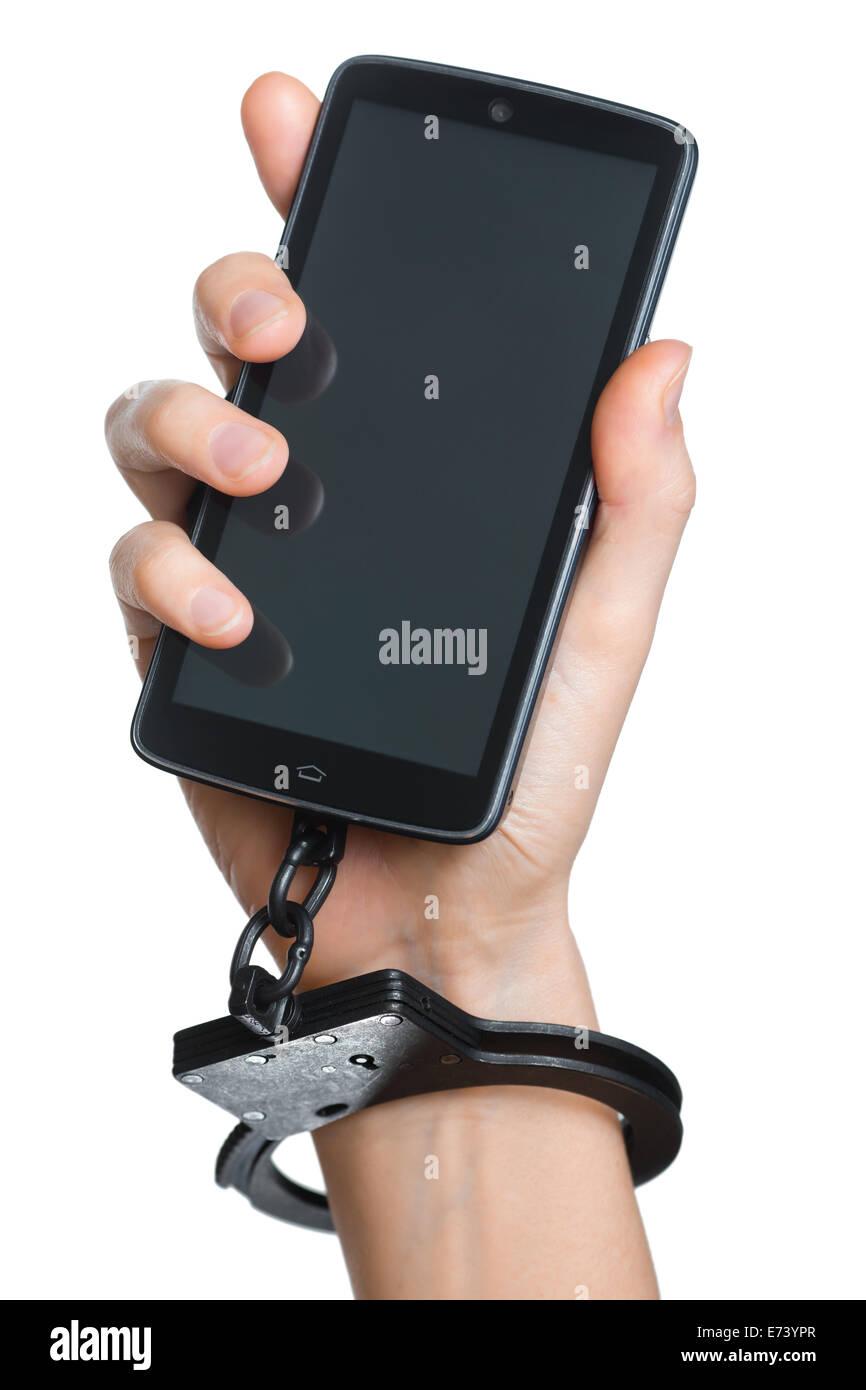 Telefono cellulare la dipendenza del concetto. Smartphone e manette in mano isolato su bianco. Immagini Stock