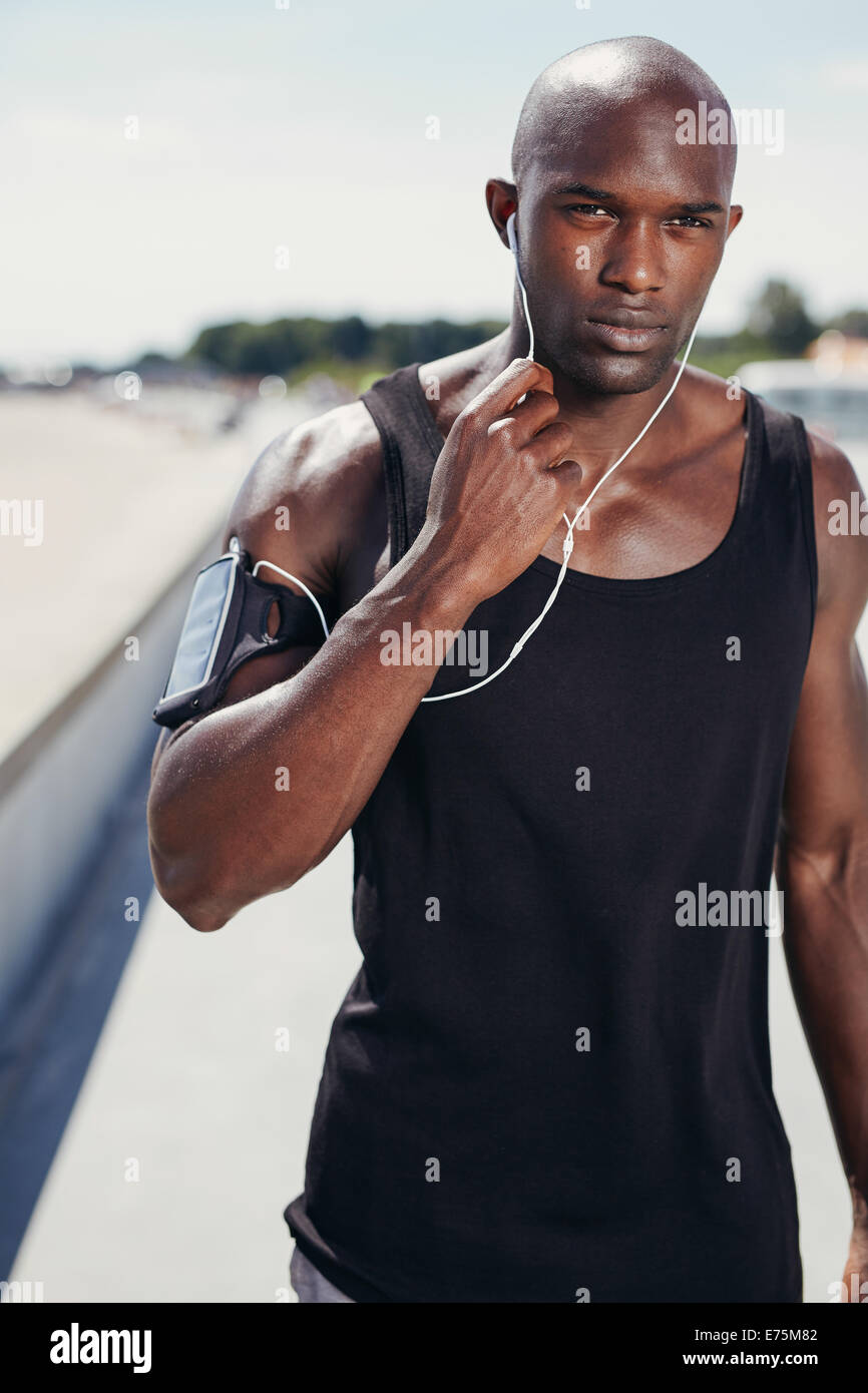 Ritratto di montare il giovane uomo all'aperto ascoltando musica in cuffia. Muscolari sane uomo con fascia per Immagini Stock