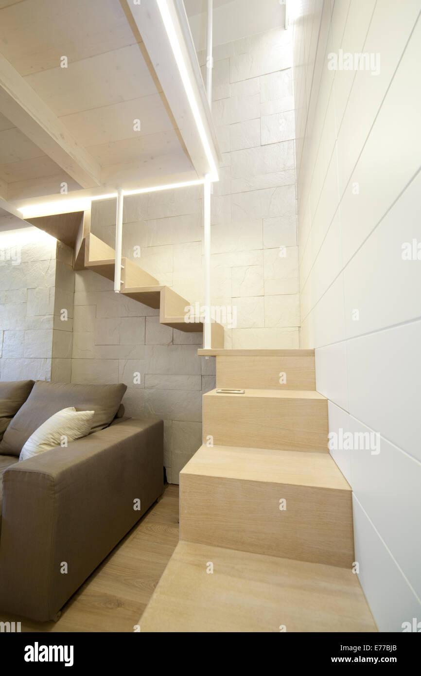 Soggiorno moderno con scale per una spazio nascosto al piano di ...