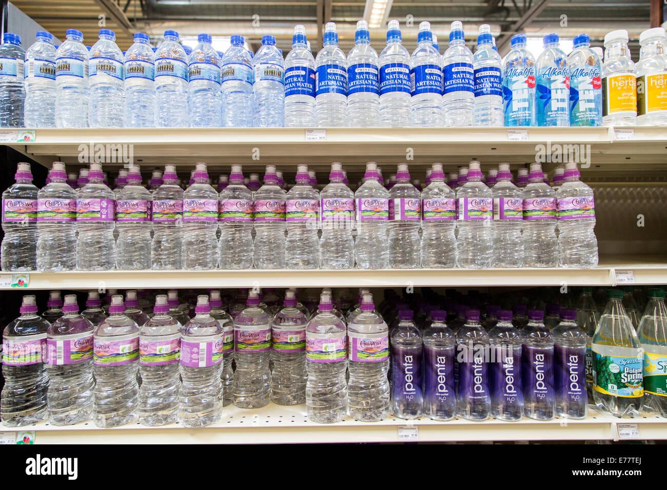 Un alimenti naturali fruttivendolo corsia con ripiani di acqua in bottiglia. Immagini Stock