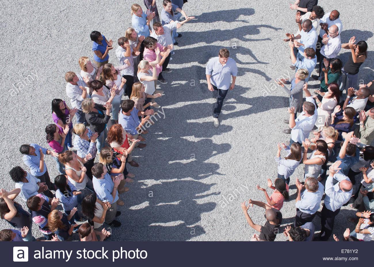 Uomo che cammina tra due gruppi di persone, persone che applaudono Immagini Stock