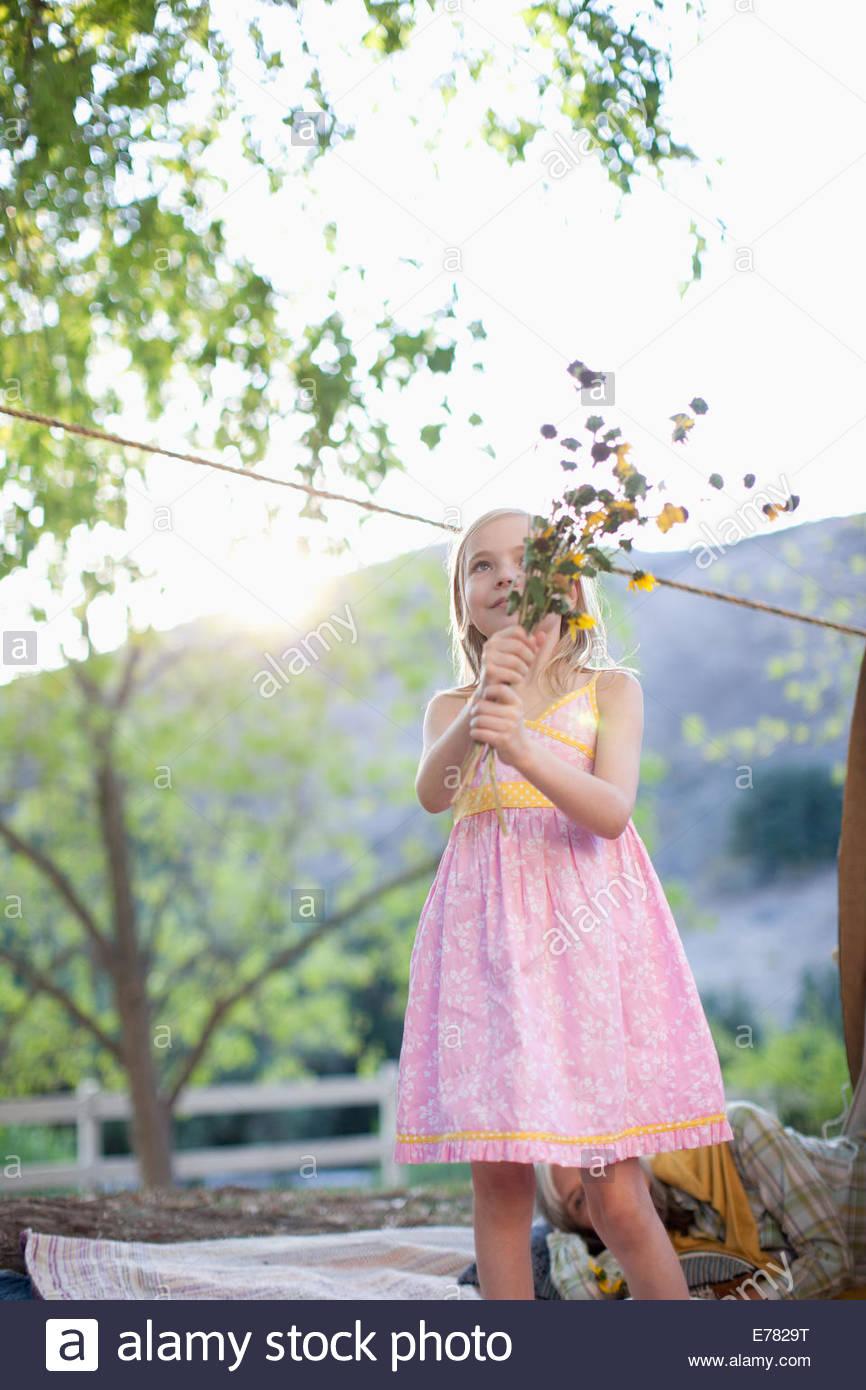 Ragazza con mazzo di fiori su una coperta Immagini Stock