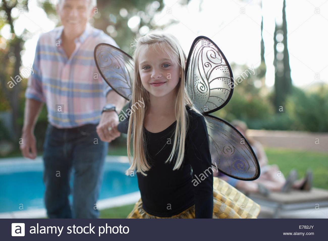 La ragazza di ali di fata tirando nonno lungo Immagini Stock