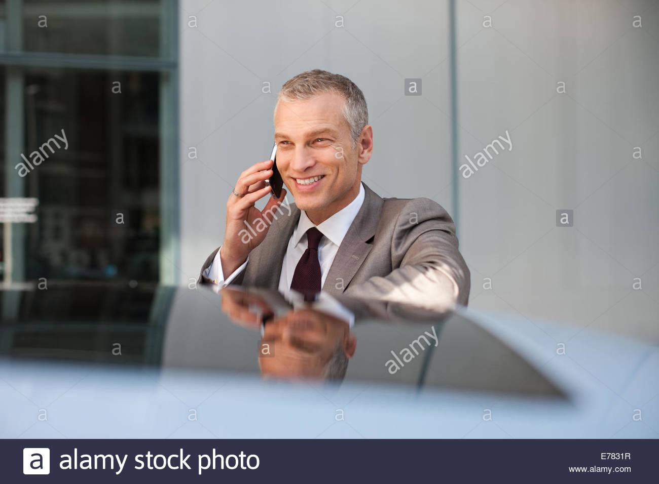 Imprenditore appoggiato su auto parlando al cellulare Immagini Stock