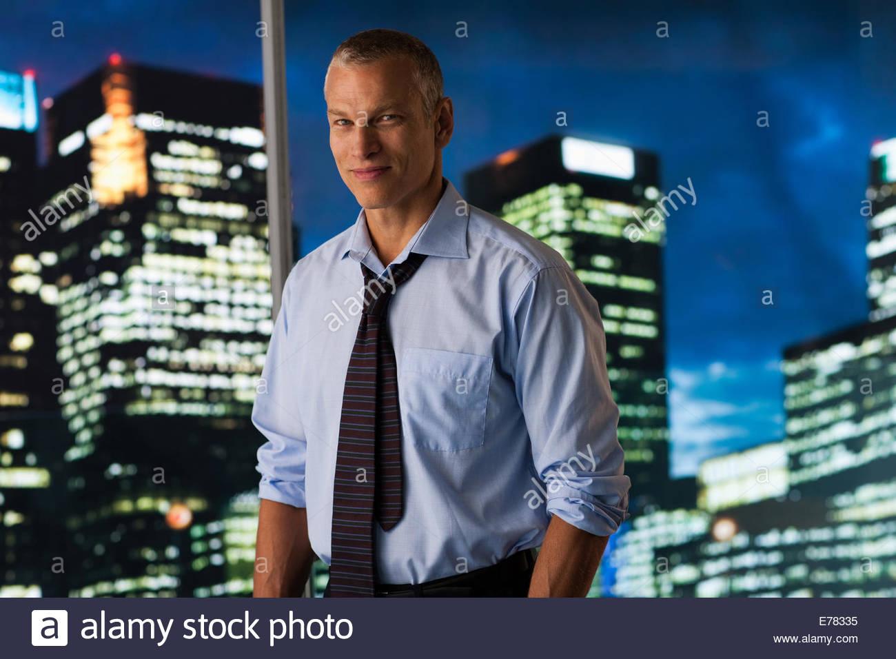 Imprenditore gravi in piedi alla parete in vetro con paesaggio urbano in background Immagini Stock