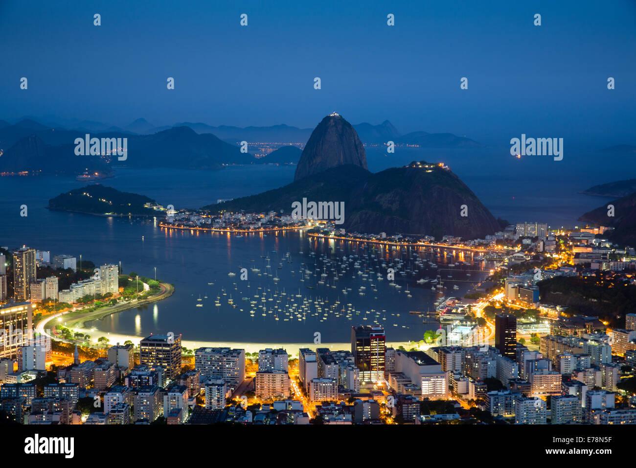 La baia e la città, e la Montagna Sugar Loaf al crepuscolo, Rio de Janeiro, Brasile Immagini Stock