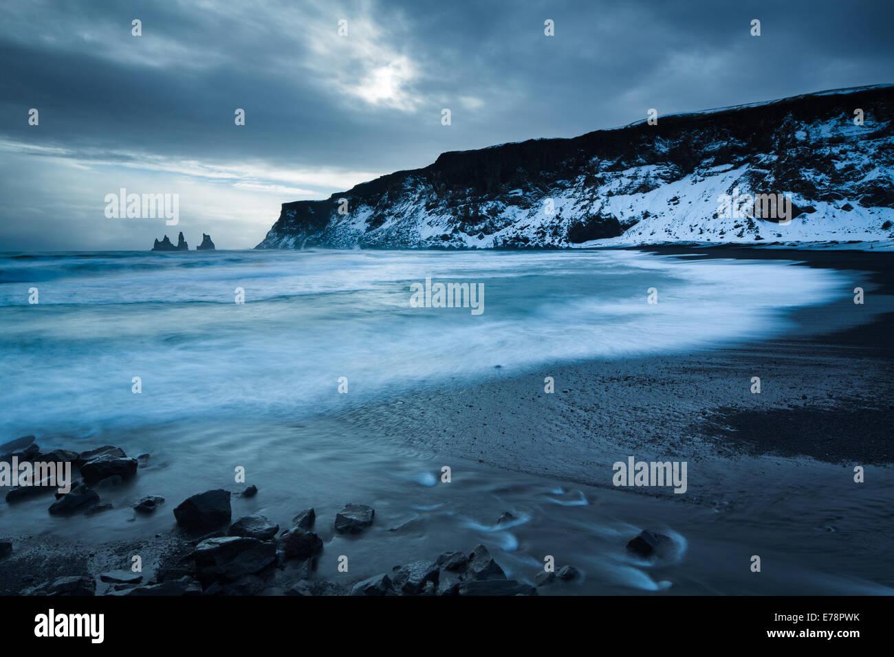 La spiaggia di sabbia nera a Vík í Mýrdal in inverno, con il basalto Renisdrangar mare pile al di là, sud dell'Islanda Foto Stock