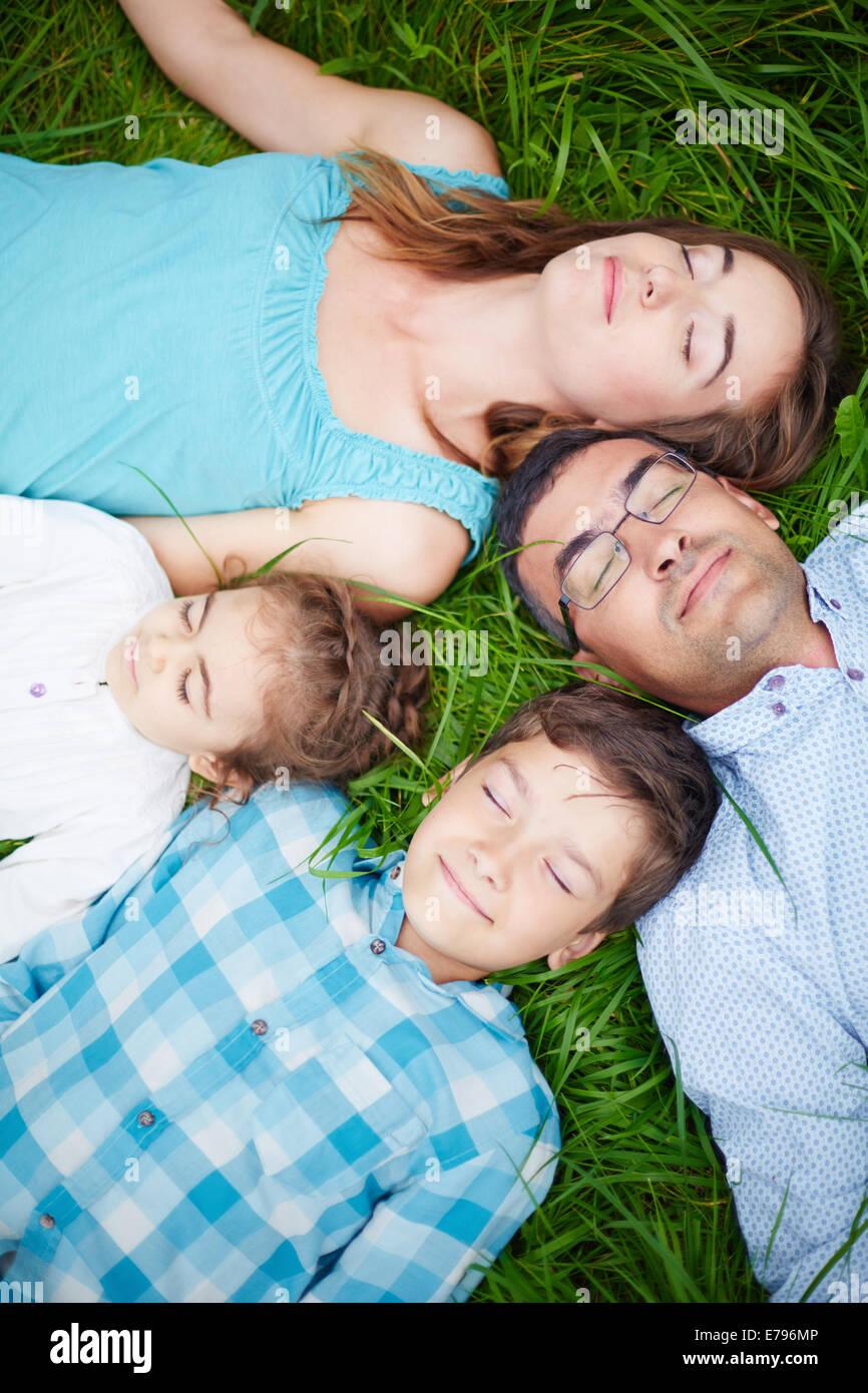 Serena famiglia di quattro rilassanti sull'erba con gli occhi chiusi Immagini Stock