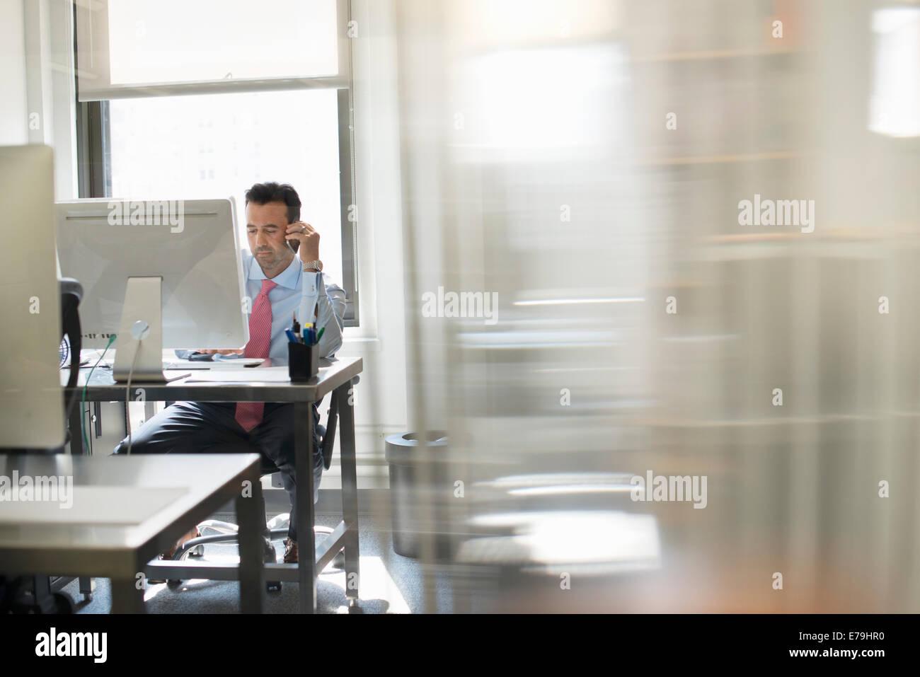 Un uomo seduto allo schermo di un computer al lavoro sul suo proprio. Immagini Stock