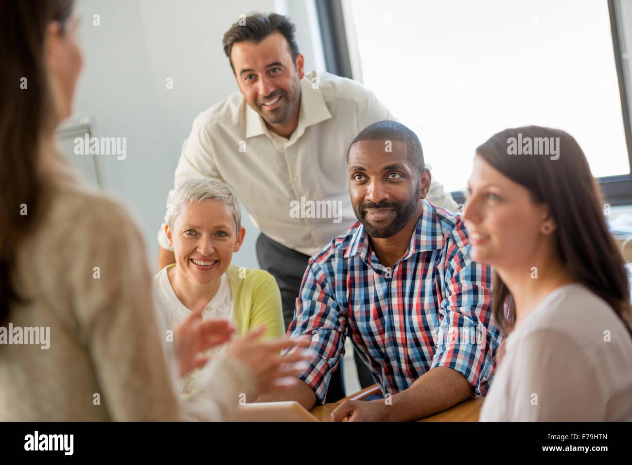 Cinque persone in un ufficio, due uomini e tre donne parlare. Immagini Stock