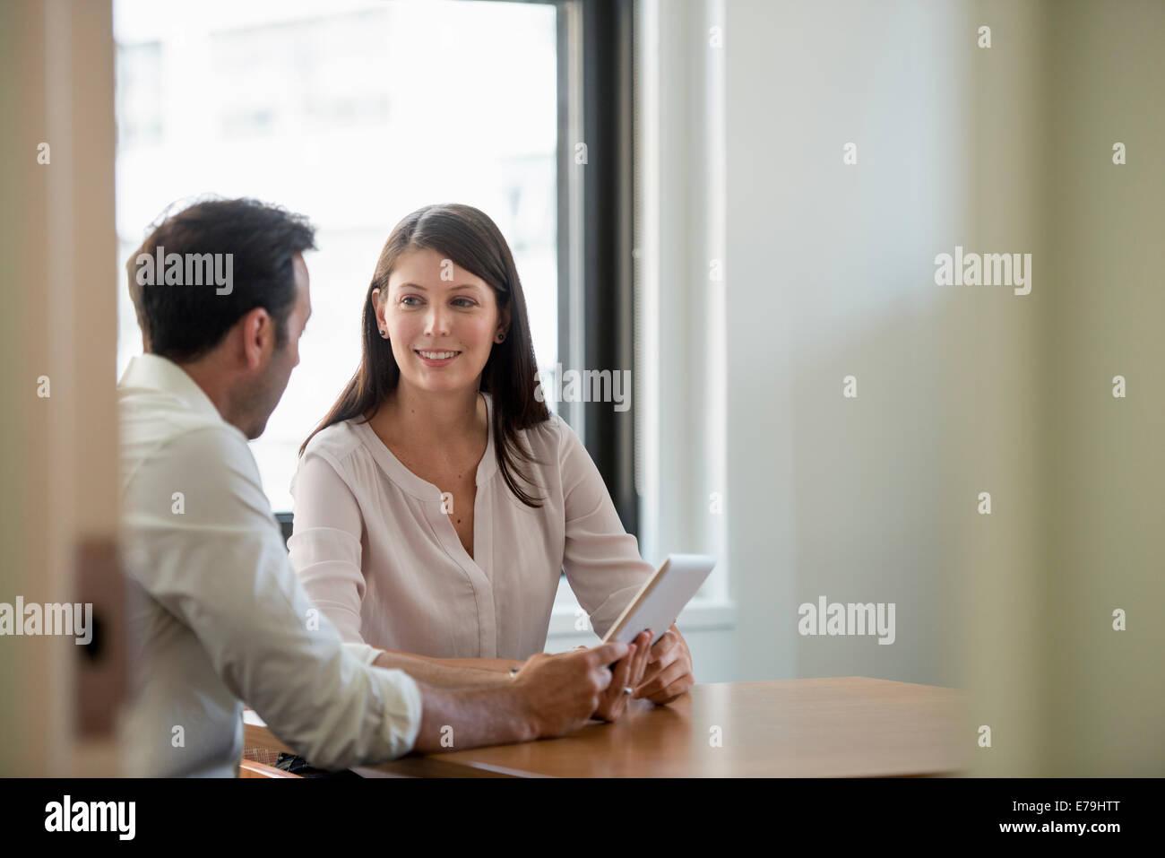 Un uomo e una donna in un ufficio, la condivisione di una tavoletta digitale. Immagini Stock