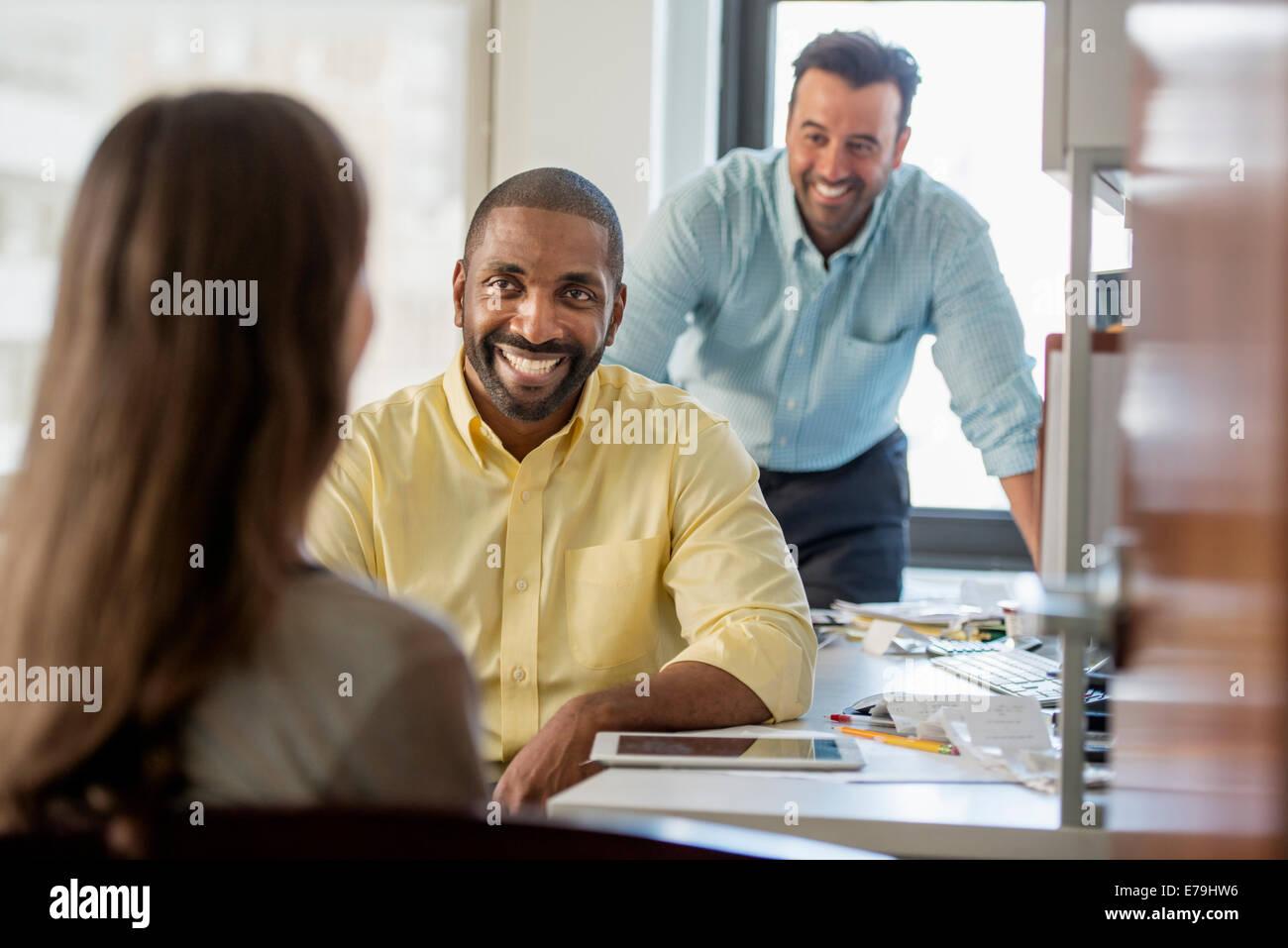 Tre persone in un ufficio, due uomini e una donna con il computer e il monitor digitale compressa. Immagini Stock