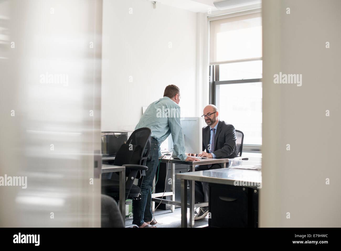 Vita in ufficio. Due persone che parlano tra di loro su una scrivania. Immagini Stock