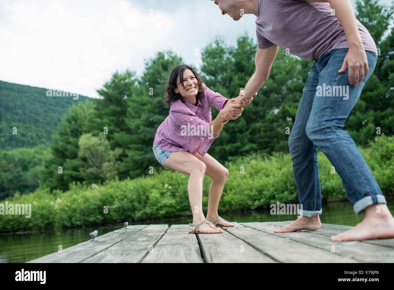 Una coppia che cerca di tirare ogni altro nell'acqua fuori un pontile Foto Stock