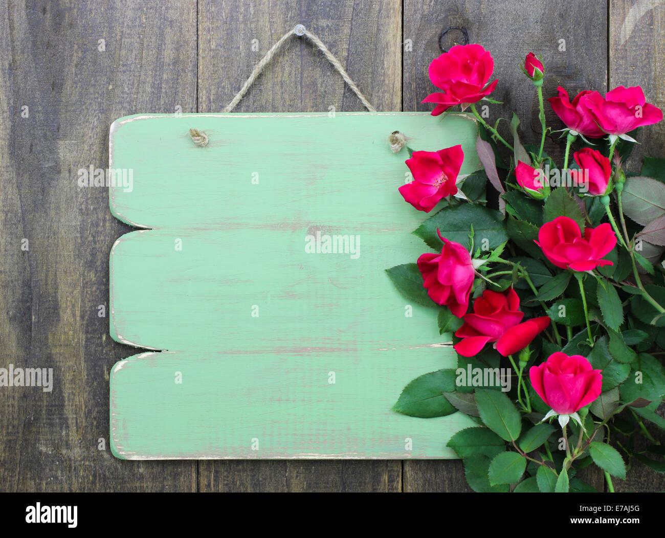 Addolorato vuoto segno verde con bordo di fiori di rose rosse appese su legno rustico sfondo Foto Stock