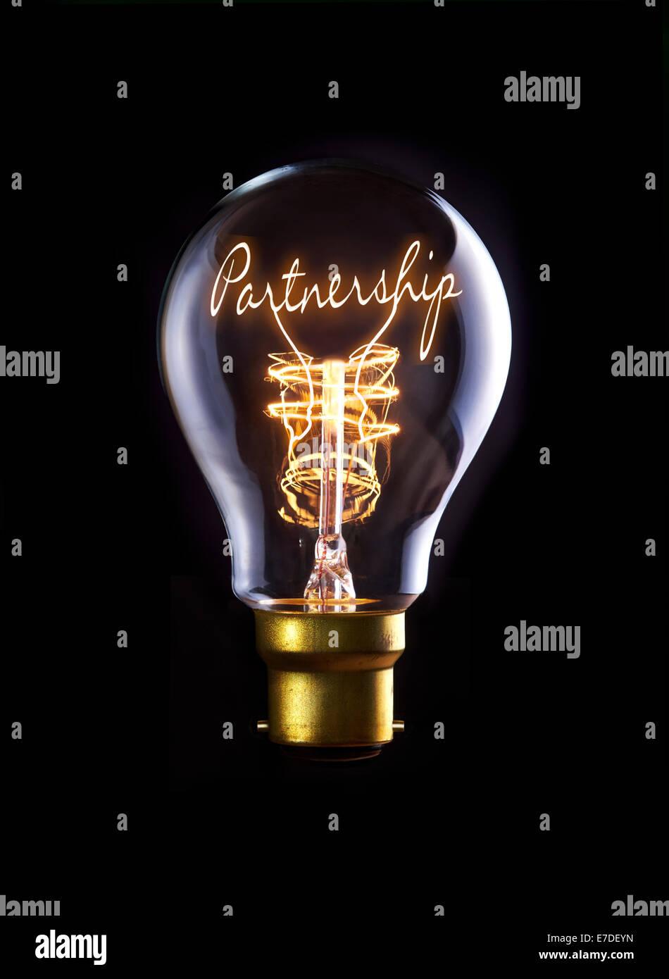 Il concetto di partenariato in un filamento lampadina. Immagini Stock