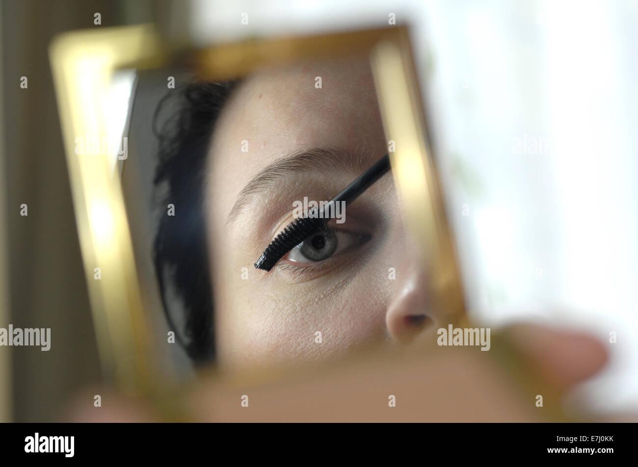 Le belle donne alla ricerca di una mano specchio mentre utilizzando uno spazzolino per mascara Foto Stock