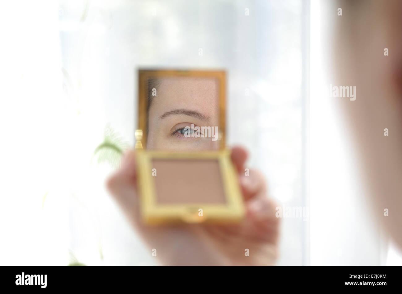 Pretty Woman tenendo una mano specchio guardando la sua riflessione Immagini Stock