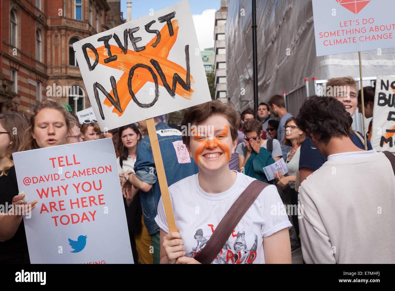 Un giovani manifestanti sorrisi come egli detiene una targhetta, chiamando per istituzioni di tutto il paese a cedere Immagini Stock