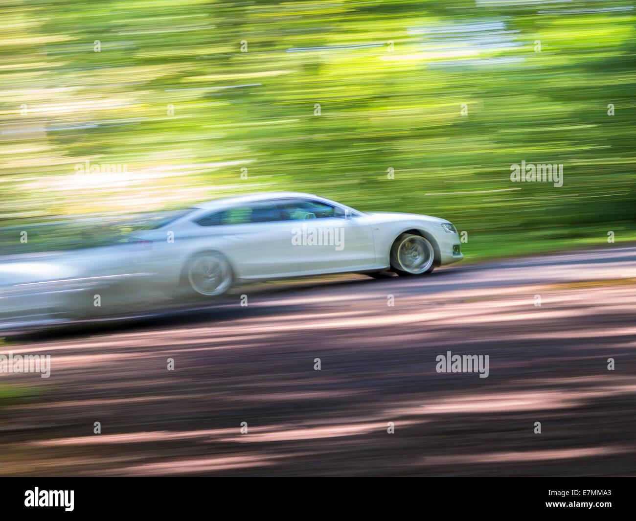 Accelerazione. Piede giù duro su una strada di bosco. Il panning, motion blur e angolazione della telecamera Immagini Stock