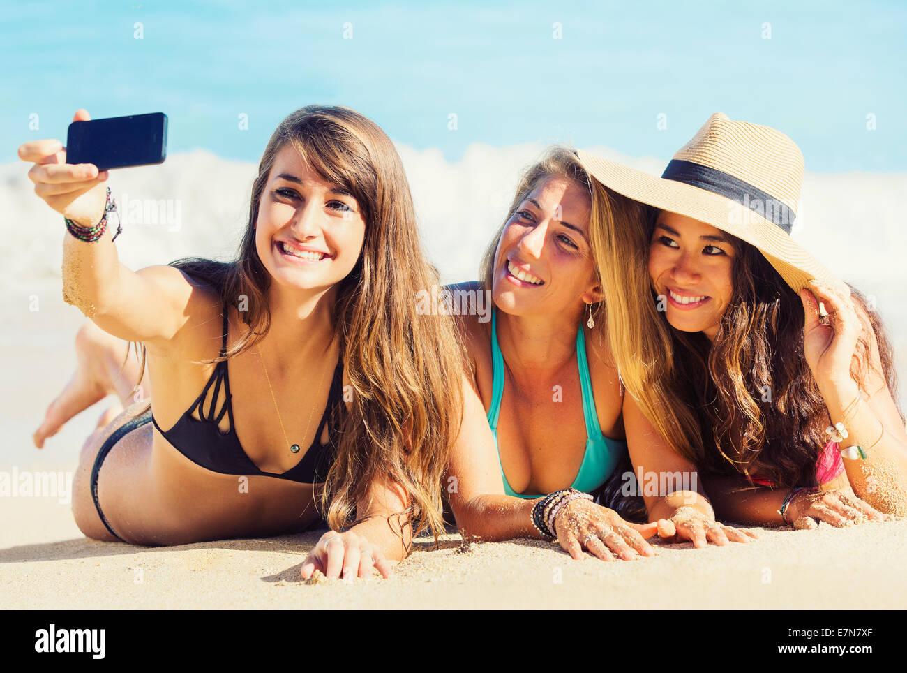 Le ragazze per divertirsi in spiaggia prendendo autoritratto con smart phone. Divertimento estivo stile di vita. Immagini Stock
