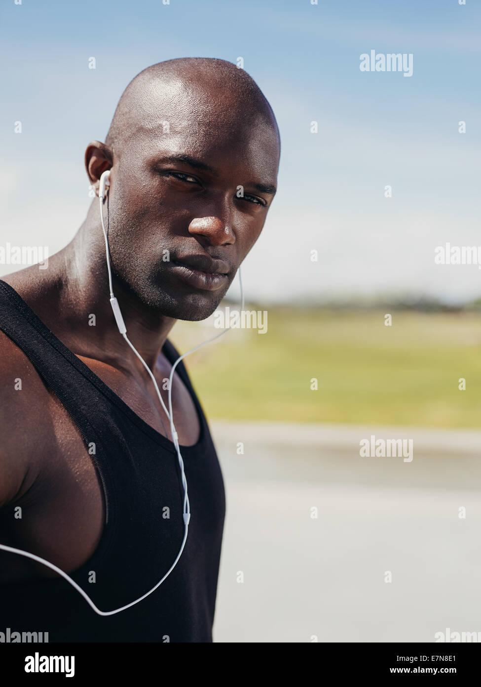 Immagine del bel giovane uomo che indossa gli auricolari guardando la fotocamera. African maschio modello all'esterno. Immagini Stock