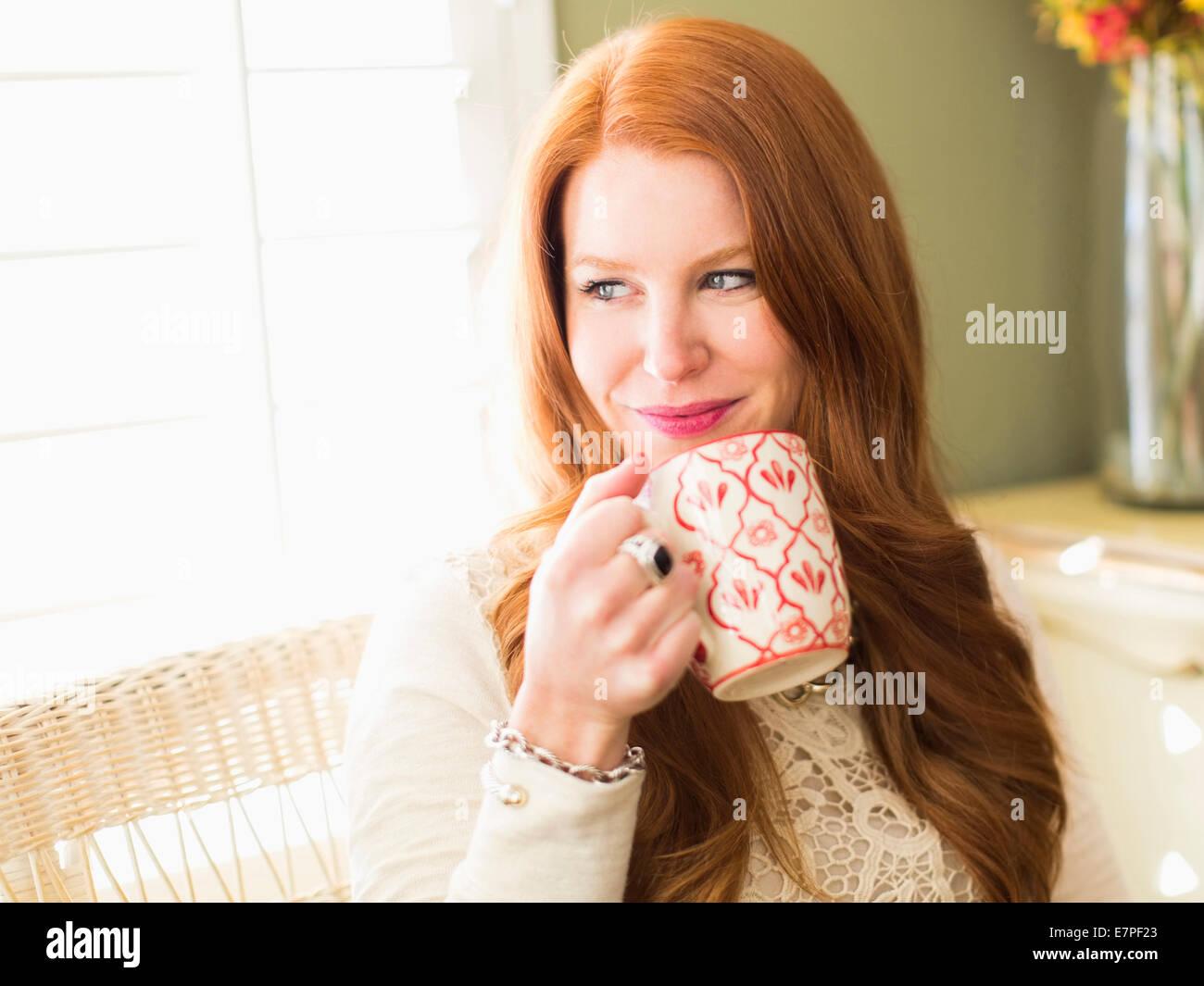 Metà donna adulta di bere dalla tazza da caffè Immagini Stock