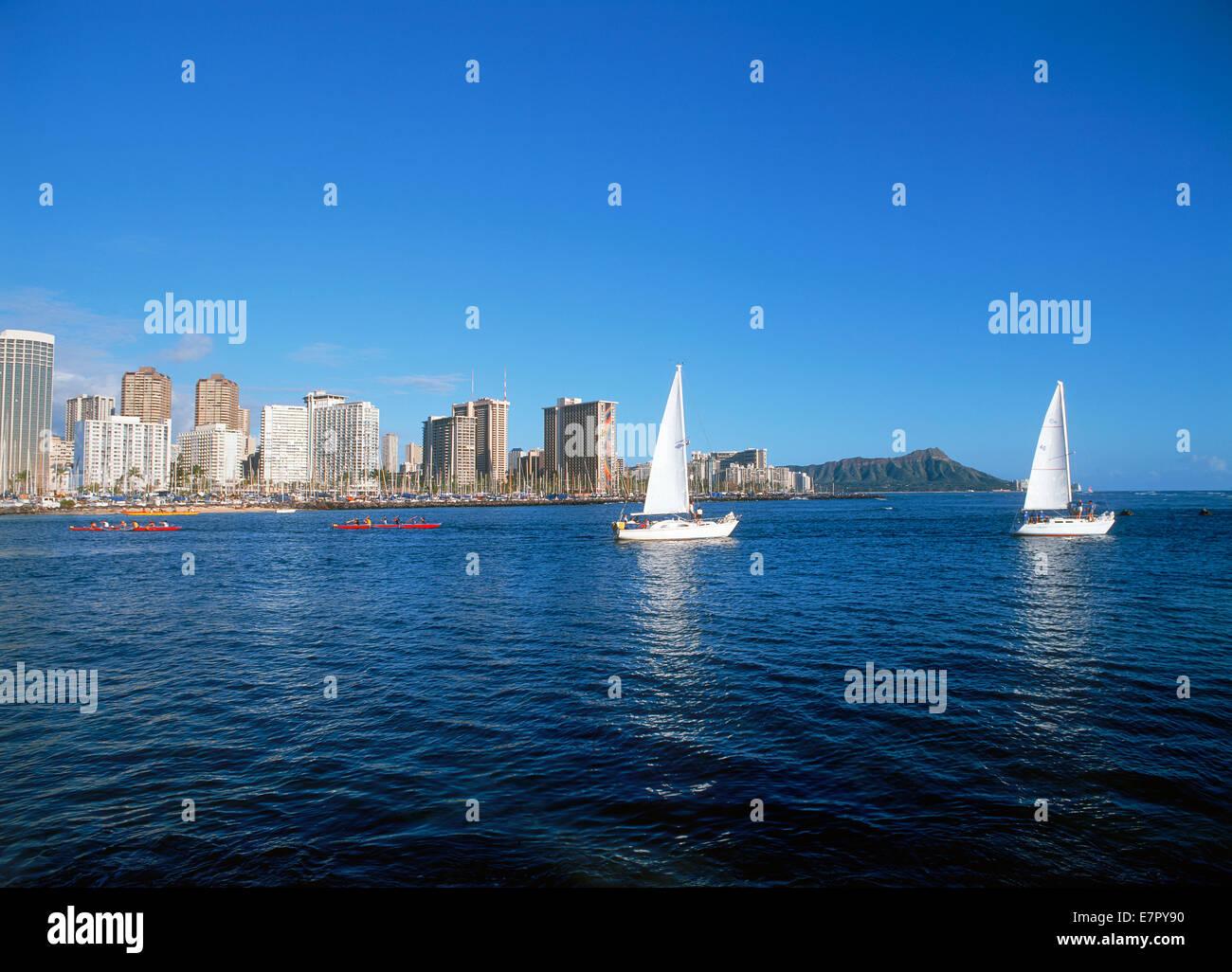 Canoe Outrigger e barche a vela lasciando Ala Wai Harbour con Diamond Head e Waikiki hotel visto dalla magica isola Immagini Stock