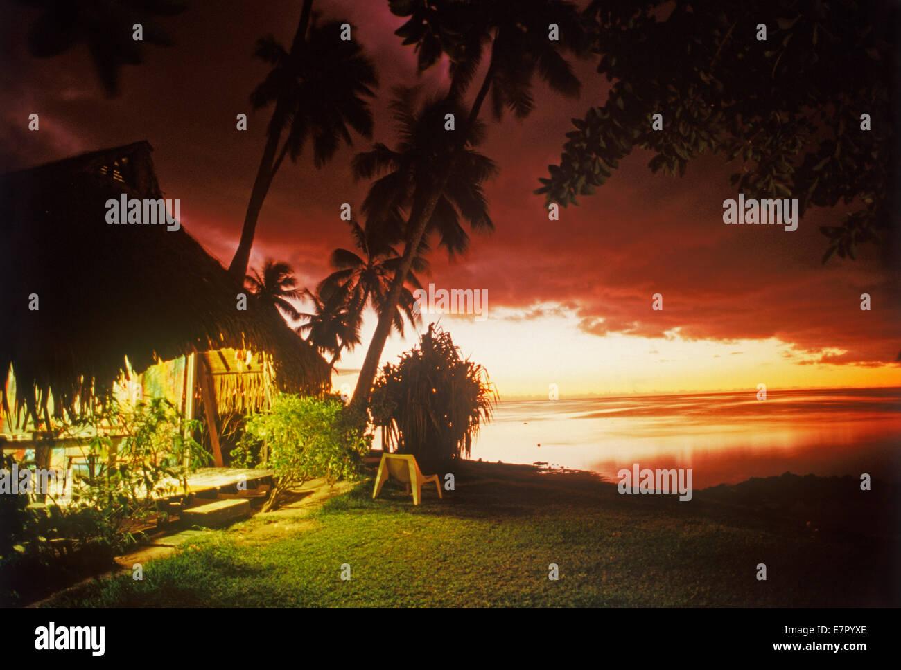 Capanna illuminata al tramonto sull'Isola di Moorea in Polinesia francese Immagini Stock