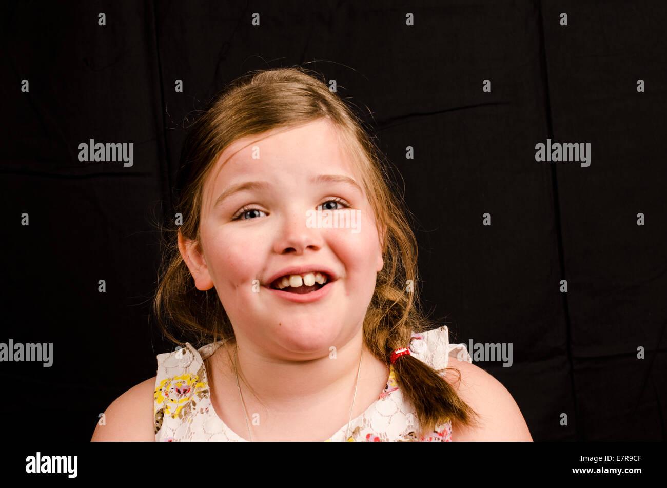 Immagine di una bimba di 8 anni, su uno sfondo nero con una felice espressione che mostra la contentezza Immagini Stock