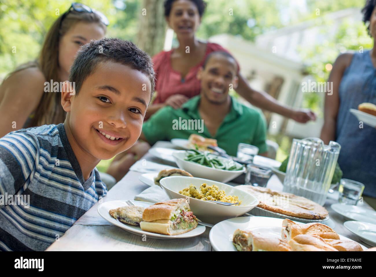 Una riunione di famiglia, uomini, donne e bambini intorno a un tavolo in un giardino in estate. Un ragazzo sorridente Immagini Stock