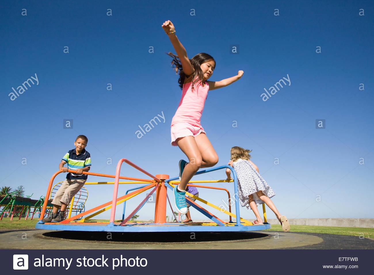 I bambini di saltare fuori merry-go-round al parco giochi Immagini Stock