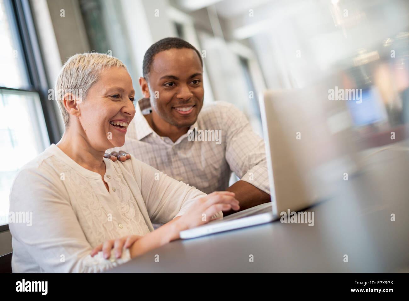 Vita in ufficio. Due persone, un uomo e una donna che guarda uno schermo portatile e ridere. Immagini Stock