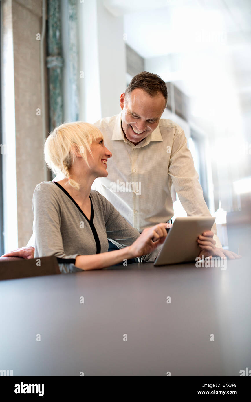 Vita in ufficio. Due persone che condividono un tavolo digitale in un ufficio. Immagini Stock