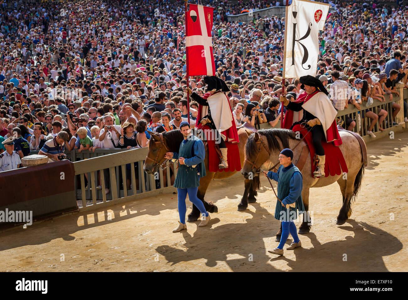 Sfilano le compagnie di bandiera su cavalli al corteo storico prima del Palio di Siena corsa di cavalli, Siena, Immagini Stock