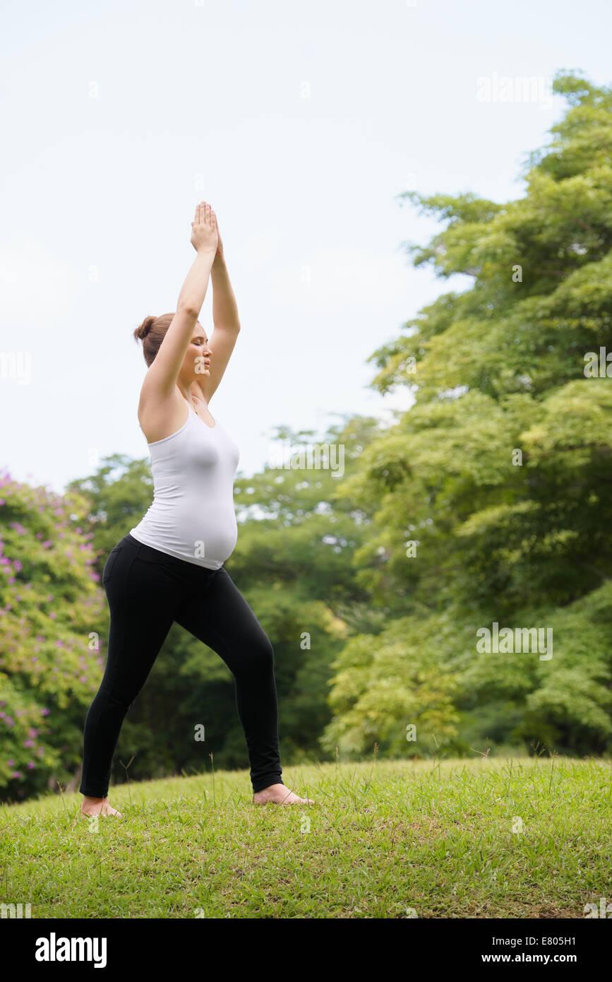Donna incinta fare yoga in posizione di parcheggio Immagini Stock