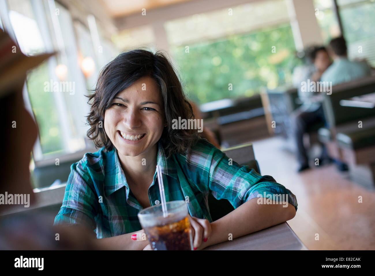 Una donna seduta tenendo un drink freddo a un tavolo da pranzo. Immagini Stock