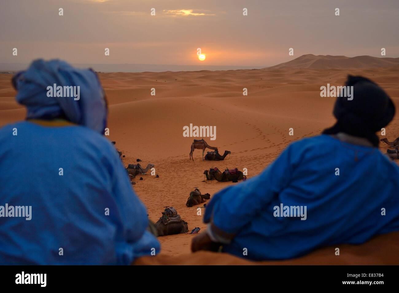 Berber uomini guardando sunrise, Erg Chebbi, il deserto del Sahara, Merzouga, Marocco Foto Stock