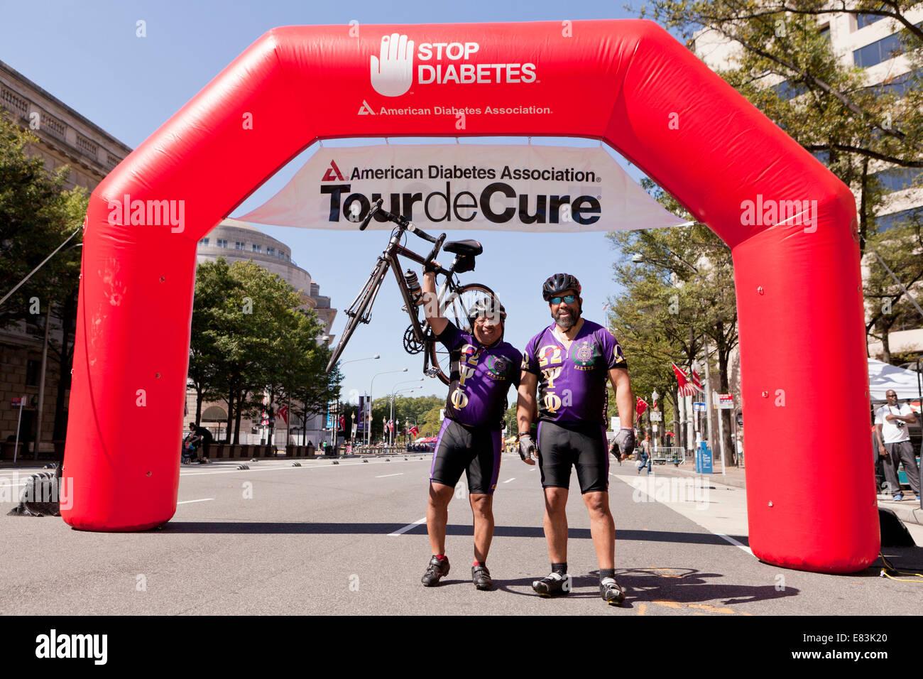 Gli uomini celebrando al traguardo del Tour de curare, American Diabetes Association in bicicletta - Washington Immagini Stock